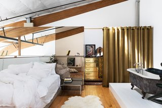 Breer designed a glass wall to section the closet and act as a headboard in the bedroom area, where a black clawfoot tub is across from the bed. The gold dresser is vintage Sarreid.