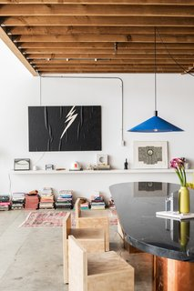 For the dining area, Breer custom-designed a table with a brass base and a marble top. A set of minimalist wood chairs and a bright blue pendant made by Simon LeComte, owner of Amsterdam Modern, complete the tableau.