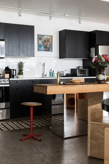 """The kitchen is outfitted with black-painted cabinetry and an island Breer crafted using a vintage, stainless-steel console and a butcher-block top. """"The stool is a gift from my friend Ellen LeComte at Amsterdam Mondern,"""" Breer says. """"I fell in love with the patina."""""""