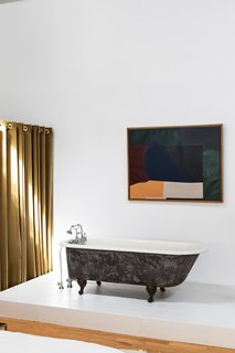 An abstract painting by modern artist Robert Breer, the designer's father, hangs above a black clawfoot tub.