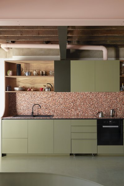 After: Pink-toned terrazzo tile counters and a backsplash and olive green-painted cabinetry enlivens the kitchen, where the designers created open shelving using leftover plywood from the mezzanine ceiling panels.