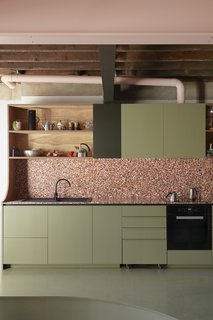 Pink-toned terrazzo tile counters and a backsplash and olive green-painted cabinetry enlivens the kitchen, where the designers created open shelving using leftover plywood from the mezzanine ceiling panels.