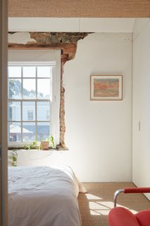 Seagrass flooring and exposed brick and bluestone around a window in one of the bedrooms.