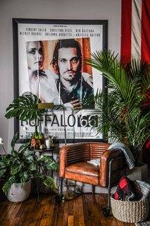 A corner Carter arranged with a leather-upholstered chair on casters from Dot & Bo and a Buffalo 66 movie poster.