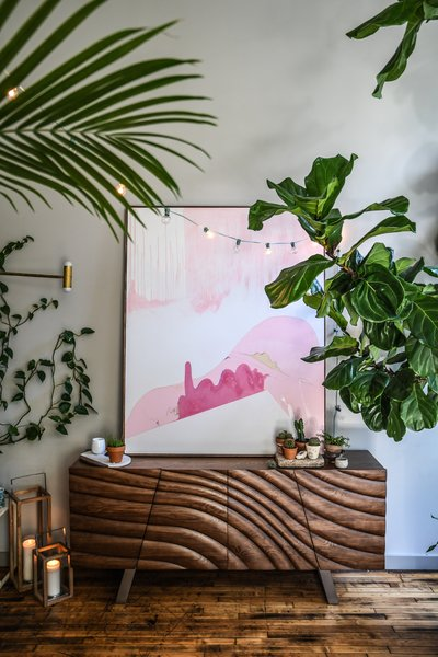 A painting by Carter hangs above a wood credenza in the work studio.