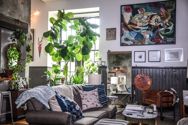 The living room, where a large industrial-style window facilitates plenty of sunlight.