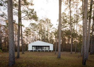 The metal-clad tiny house that architect Will Randolph of Archimania designed for his uncle and aunt, Jon and Niki Nash, stands in a natural clearing surrounded by pine, oak, and hickory trees in Okitebbeha County, Mississippi.