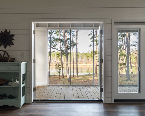 """French doors by Jeld-Wen open the living room to the terrace and the landscape beyond. The mint-green shelving unit is original to Jon's grandparents' house, which originally stood on the property. """"It holds much sentimental value,"""" he says."""