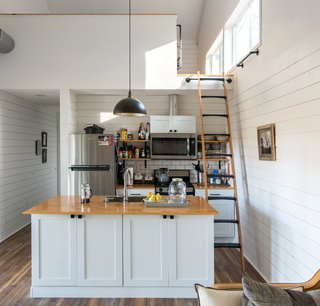 The mezzanine above the open-plan kitchen is a loft bedroom with a set of twin beds, where guests can sleep.