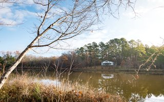 The tiny house is perched at the edge of a large pond on the property.