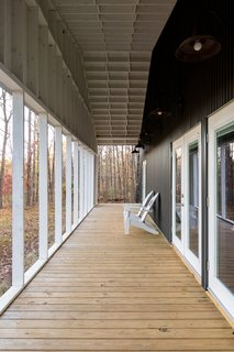 Pine decking on the porch adds warmth to the home's exterior, which is sided with metal.