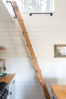 White-painted pine shiplap interior siding creates a classic look for the interior, where a kitchen ladder, built by Jon Nash, accesses the loft bedroom. The counters are lacquered plywood.