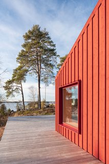 Red-painted pinewood wraps around the exterior of a tiny house that sits on a slope overlooking the Baltic Sea in the Stockholm archipelago.