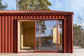 Strategically placed windows and doors open the red-painted pine plywood house to the outdoors and frame views of the landscape.