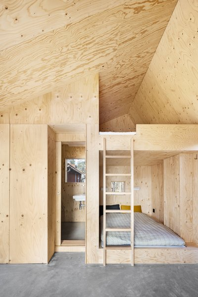 Lookofsky outfitted the bedroom with built-in pine plywood bunkbeds, walls, and a ceiling. The bathroom and a closet are also wrapped in plywood.