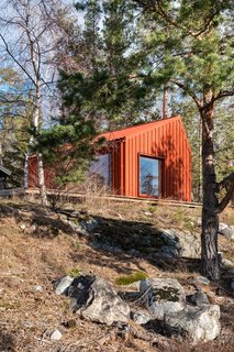 A couple's 269-square-foot getaway features a crimson exterior and an unfinished pine plywood interior.