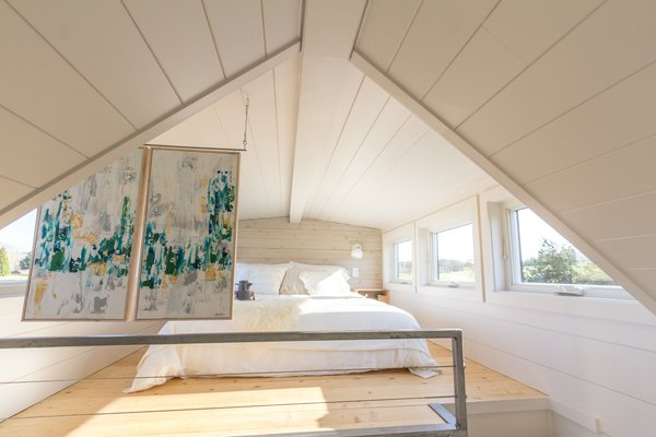 The sleeping loft accommodates a queen-size bed. Original artworks by MSusan are double-sided and help to separate the space from the other areas of the home.