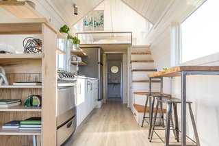 Sunlight bounces off white-painted shiplap walls in the kitchen and the sleeping loft; the flooring is from Pergo.