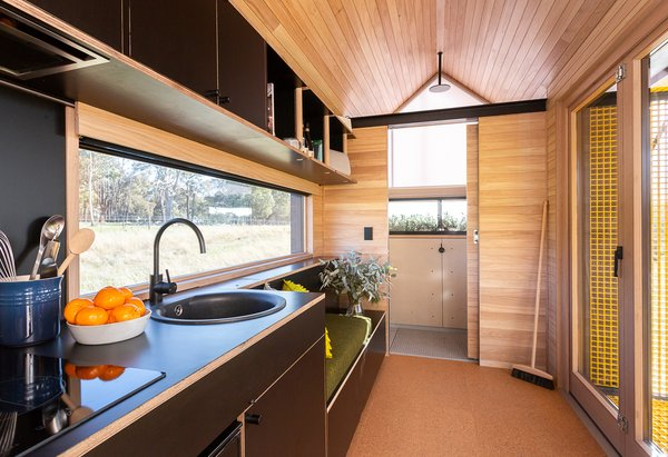 Maddison and Newstadt outfitted the interior with pre-finished cork flooring by Readycork from Premium Floors Australia. Black-painted cabinetry and a built-in bench offset unfinished shiplap timber ceiling and walls.