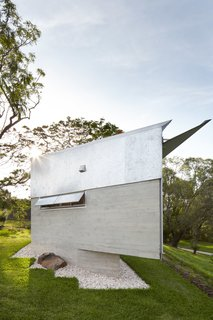 The home's oblique form is sided with board-formed concrete and galvanized metal, and it features a galvanized metal sun shade on the front facade.
