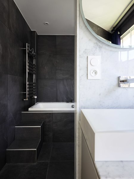 Petillault finished the bath with gray slate and white marble.