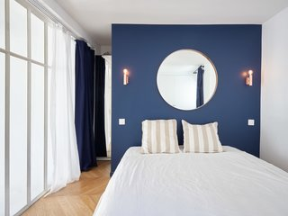 Metal sconces flank a round mirror above the bed in the mater bedroom, where a blue-painted wall adds interest.