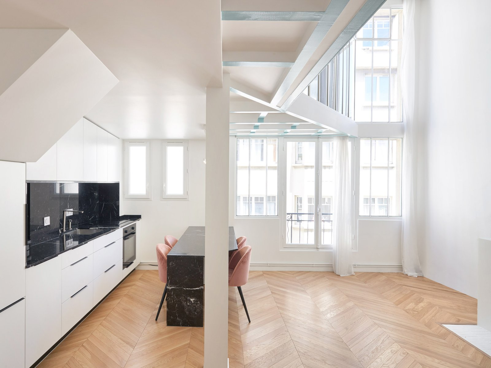 Kitchen, Wall Oven, White, Marble, Light Hardwood, Marble, and Drop In The angled mezzanine allows for a sunlight-filled kitchen-and-dining space, where oak parquet floors lend warm texture.  Best Kitchen Marble Wall Oven Photos from A Historic Paris Apartment Is Revived Using Sunlight and Bursts of Color