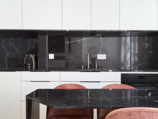 A black marble backsplash, counters and tabletop contrast with white-painted cabinetry in the kitchen-and-dining area.