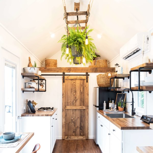 The kitchen area in the Rumspringa model features white-painted cabinetry and a sliding barn door.