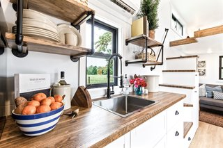 Upper wall shelves and open nooks beneath the staircase offer added storage in the Rumspringa.