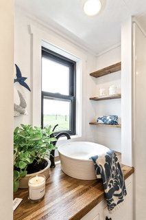 Horizontal shiplap siding offsets coffee-colored wood counters on the vanity in the bath.