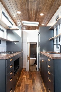Charcoal gray-painted cabinetry and leather pulls create a sleek aesthetic for the Gooseneck.