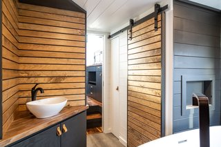 The bath in the Gooseneck is outfitted with charcoal gray and honey-colored horizontal wood siding.