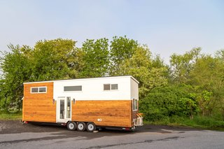 The exterior of the Modern model is wrapped in natural wood siding, which is accented with white-painted wood.