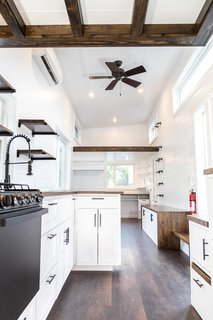 Wood floors stained the color of espresso counter the white-painted shiplap walls on the interior of the Modern model.