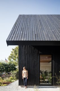 Exterior, House Building Type, Gable RoofLine, and Wood Siding Material Resident Marjon Helder stands against the black-stained vertical siding, which matches the cladding of the roof and creates a sculptural effect for the home.
