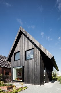 Exterior, Gable RoofLine, House Building Type, and Wood Siding Material Three strategically placed large windows mark the home's front facade, and in combination with the vertical siding and the asymmetrical roofline, lend a graphic presence.