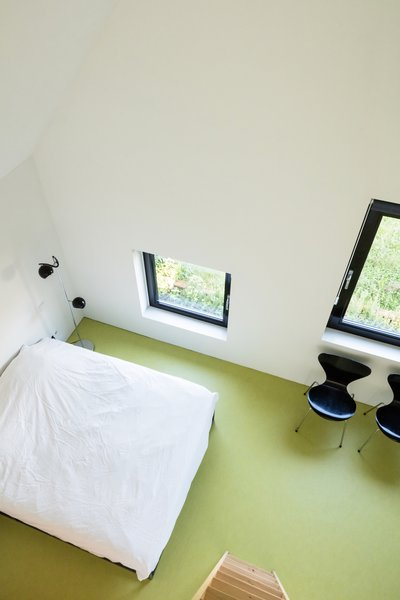 A lime green-painted concrete floor makes for a vibrant bedroom.