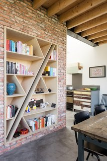 In the dining area, a custom birch bookcase is inset into a partial wall of brick that was salvaged from the previous house that stood on the lot.