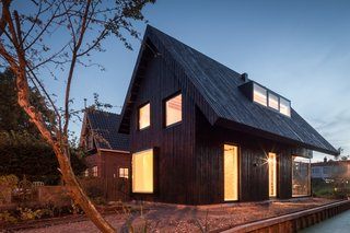 Clad in wax-covered pine, this 645-square-foot dwelling in Amsterdam is striking on the outside and endlessly charming on the inside. At night, the large windows give the compact home a lantern effect.