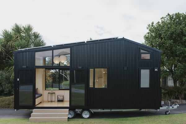The First Light tiny home is sided with black corrugated steel and features expansive windows and French doors that connect the plywood interior to the outdoors.