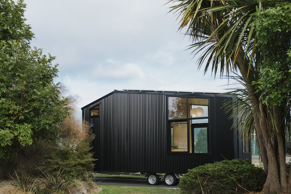 The rear facade of the steel-clad tiny home has a large window that provides ventilation and an indoor/outdoor connection.