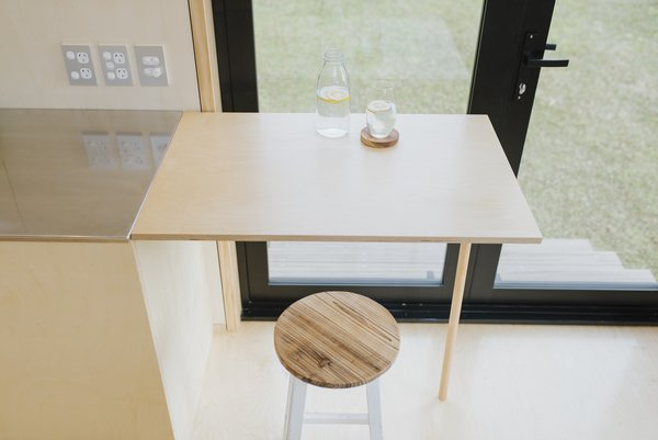 A plywood table top folds out from the kitchen cabinetry and serves as a dining table.