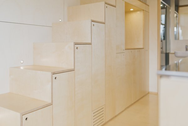 Storage cabinets are built into the underside of the plywood staircase.