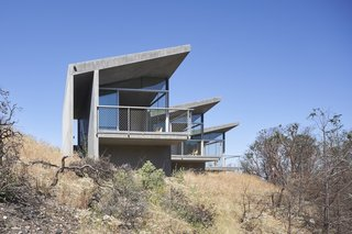 The 840-square-foot guesthouse Mork Ulnes Architects designed in Sonoma, California, comprises three concrete-and-glass volumes that line a great ridge.
