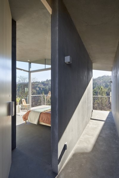 Sunlight pours through glass walls and washes over the interior's smooth, poured-in-place concrete walls, floors, and ceiling.