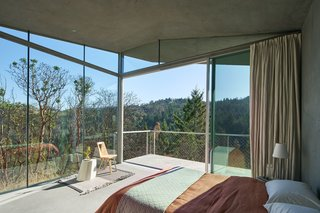 Glass walls and a concrete deck connect the guesthouse to Sonoma's lush landscape.