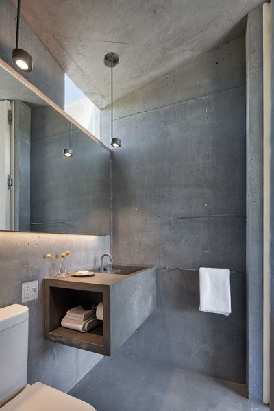 The architects outfitted the baths with smooth concrete floors, walls, ceilings—and a cantilevered vanity.