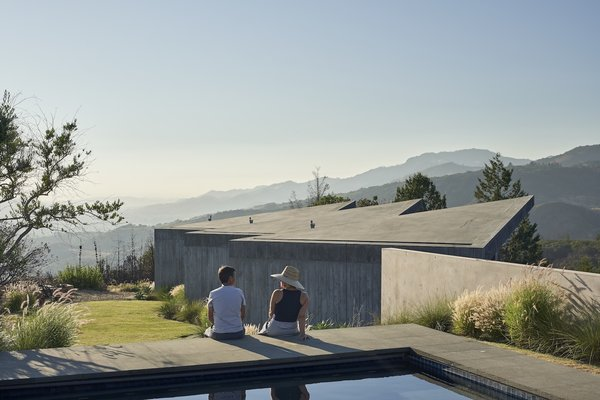 The guesthouse's staggered rooftop mimics the rolling hills of the landscape. Board-formed concrete on the exterior evokes wood siding while being low-maintenance and fire-resistant.