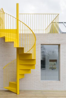 The sunshine-yellow spiral staircase stands out against the pale tone of the brick facade.